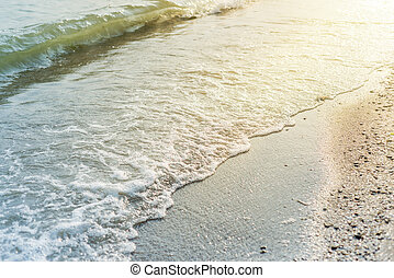 water wave over sand beach and sun reflections
