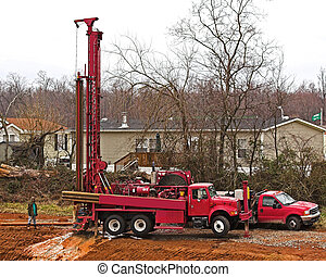 Water well driller digging new well for subdivision