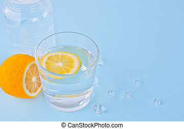 water with lemon on the blue background. Copy space.