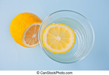 water with lemon on the blue background. Top view.