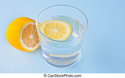 water with lemon on the blue background.