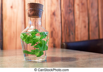 Water with mint in a glass jug on the table