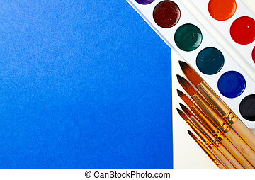 Watercolor paint box and set of brushes on blue and white background