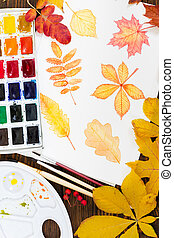 Watercolor painting with autumn leaves on wooden background.