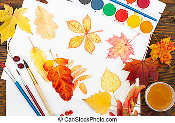 Watercolor painting with autumn leaves, paint, brushes and colorful autumn leaves