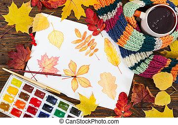 Watercolor painting with autumn leaves, paint, brushes and colorful autumn leaves on wooden background.