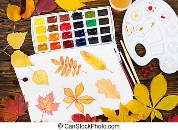 Watercolor painting with autumn leaves, paint, brushes, palette and colorful autumn leaves on wooden background.