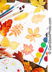 Watercolor painting with autumn leaves, paint, brushes, palette and colorful autumn leaves