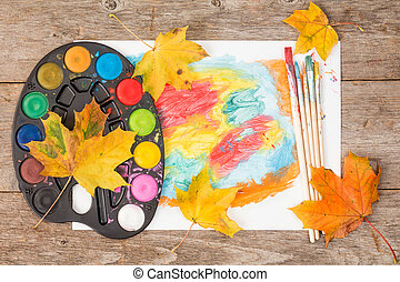 Watercolor paints and autumn leaves