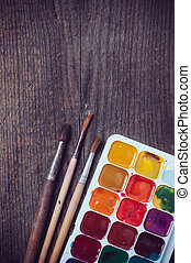 Watercolor paints and brushes, painting tools on an old wooden board.