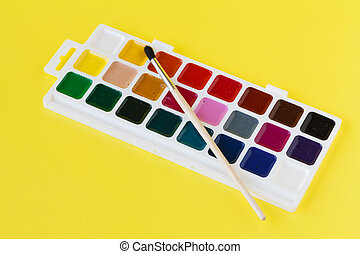 Watercolor paints in a box with a brush