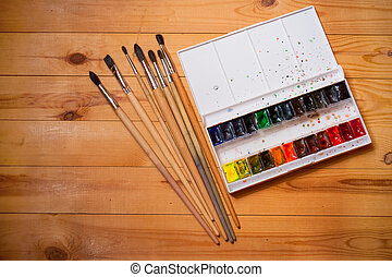 Watercolor paints in box with brushes on wooden board