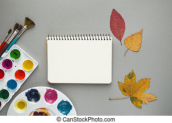 Watercolor paints with brushes on grey background.