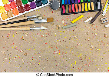 watercolor palette with paintbrushes different size and colorful pastels on desk