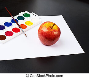 Watercolor set and apple over white paper