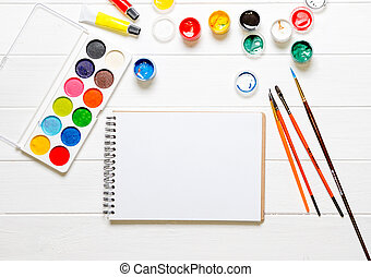 Watercolors and brushes with white notebook