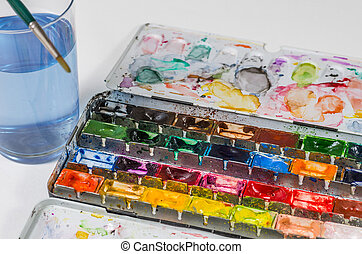 watercolors with brush and water glass