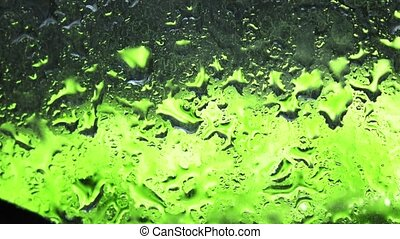 Waterdrops on glass and defocused green apples against black background