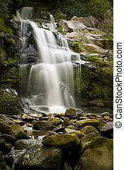 Waterfall - A waterfall surrounded by rocks and some ...