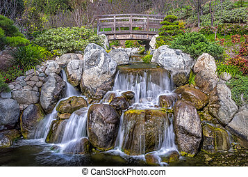 Waterfall and bridge with silky water and vibrant green foliage.