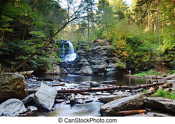 Waterfall and lake in woods in Autumn