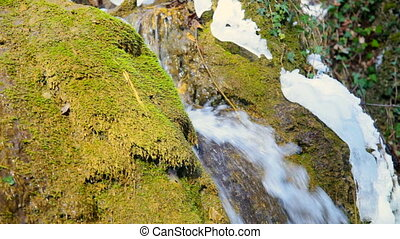 Waterfall and mossy rock in winter
