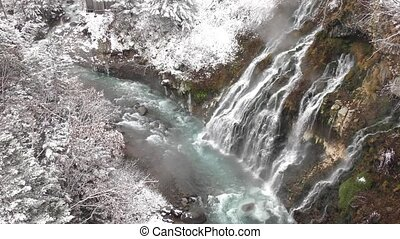 Waterfall and snowy forest - Streaky waterfall flowing on a...