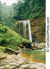 Waterfall at costa rica with big rocks in a river.