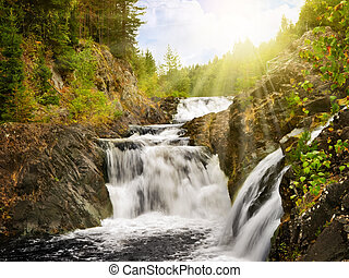 waterfall between rocks in sunny forest scenery