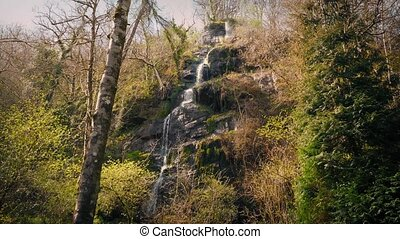 Waterfall Cascading Down Rock Face - Water flows down steep...