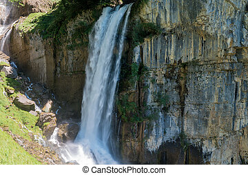 Waterfall emerging from the rocks in a forest - The...