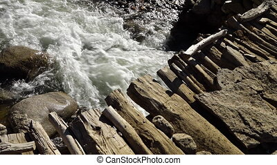 Waterfall emerging from under a bridge - A hand held, high...