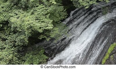Waterfall falling over rock mass - Close up thin white...