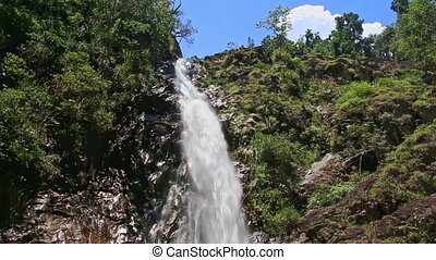 Waterfall from Top among Green Rocks along Foamy Stream to...