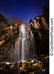 Waterfall in moonlight with stars