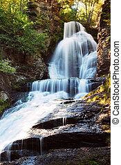 Waterfall in Autumn mountain with woods, foliage and rocks. Digman Fall of Pennsylvania
