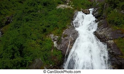 Waterfall in mountains of Norway in rainy weather from air...