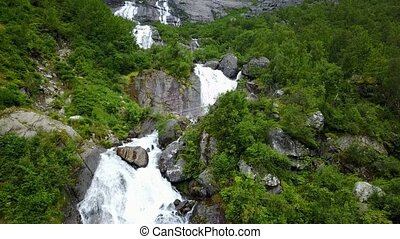 Waterfall in mountains of Norway in rainy weather from air view from drone