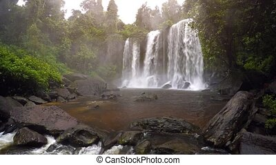 Waterfall in rainforest. Overcast weather. Phnom Kulen Park,...