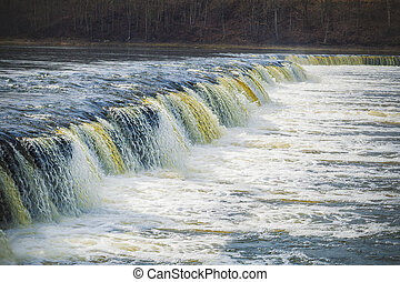 Waterfall in river in early spring