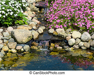 waterfall in rock garden with pond