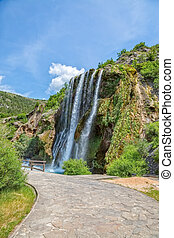 Wide shot of waterfall Krcic flows into the river Krka in Knin.