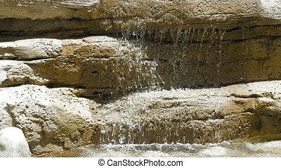 Waterfall on big rocks while the sun is shining. Waterfall...