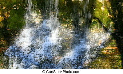 Waterfall on eroded limestone rock during summertime in the woods