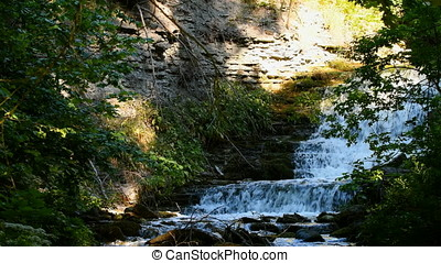 Waterfall on eroded limestone rock during springtime - Fast...