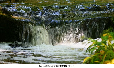 Waterfall on eroded limestone rock during summertime in the...