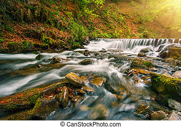 Waterfall on mountain river in autumn forest under bright sun