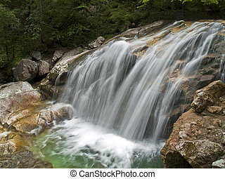 Waterfall of alpine mountain river shot with long exposure