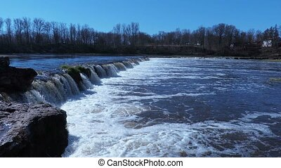 Waterfall on river in spring