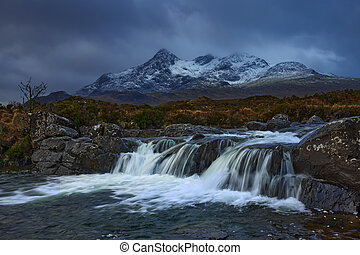 Waterfall on River Sligachan on the Isle of Skye Scotland with large mountains of the Cuillin with snow in winter, Isle of Skye, Scotland